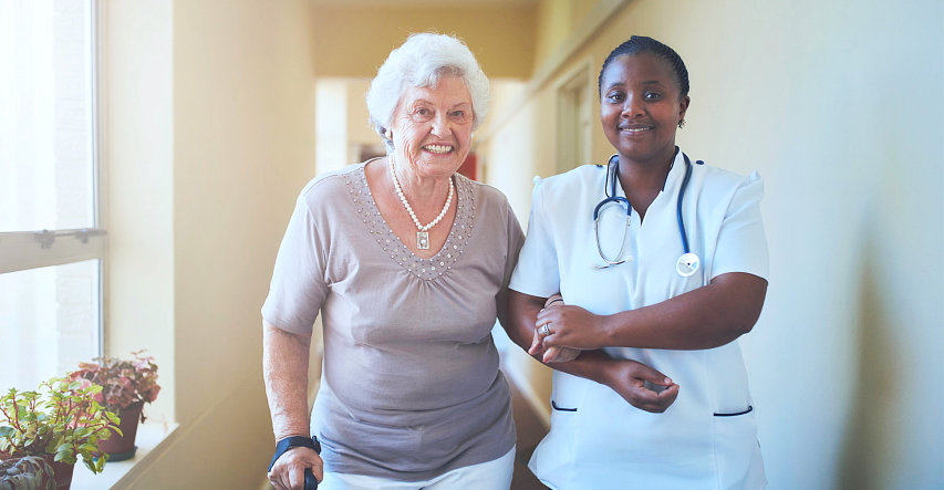 nurse assisting elderly woman in walking