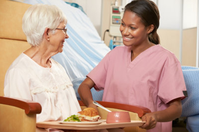 caregiver giving food to her elderly patient