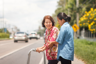 caregiver assisting woman in walking