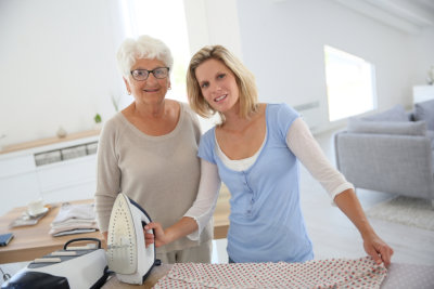 caregiver ironing her patient's clothes