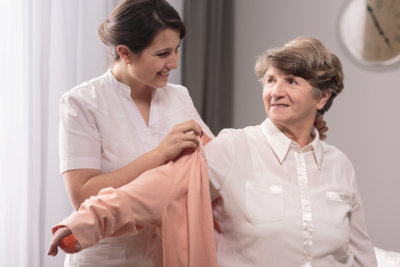 caregiver dressing her patient